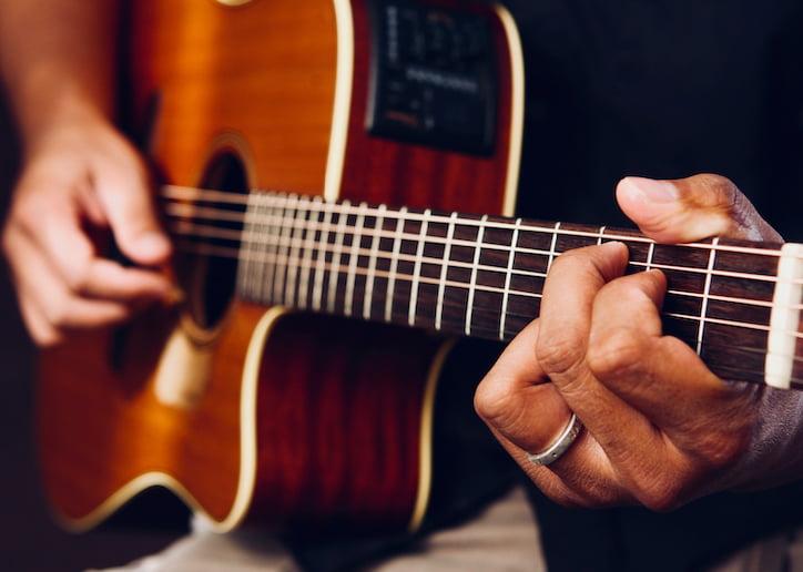 primer plano de hombre tocando guitarra acústica