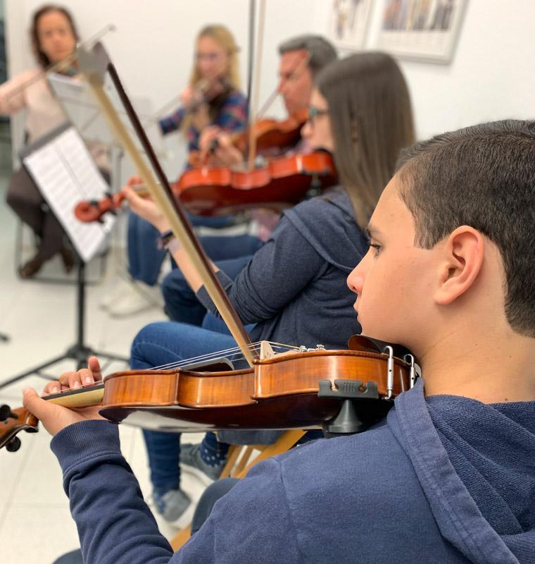 agrupación de cuerda de jóvenes y adultos ensayando en clase