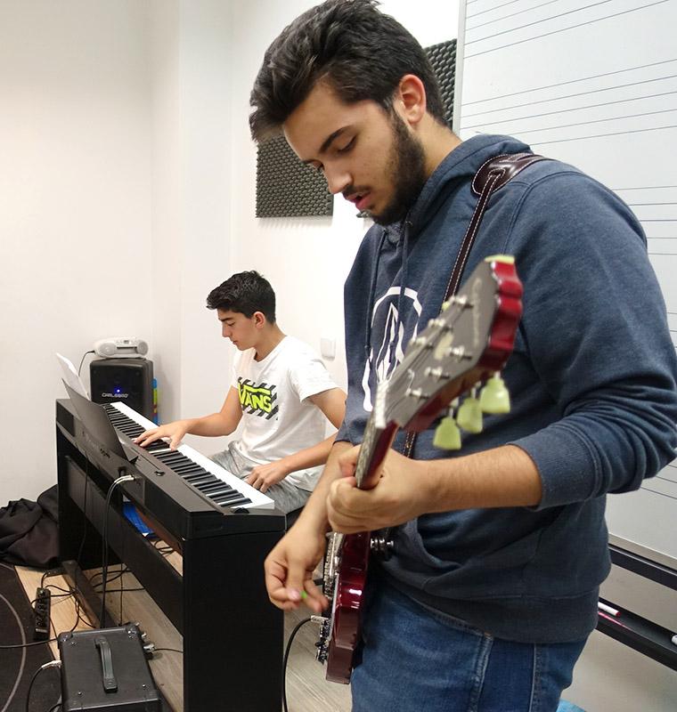 chicos jóvenes tocando la guitarra eléctrica y el teclado en clase