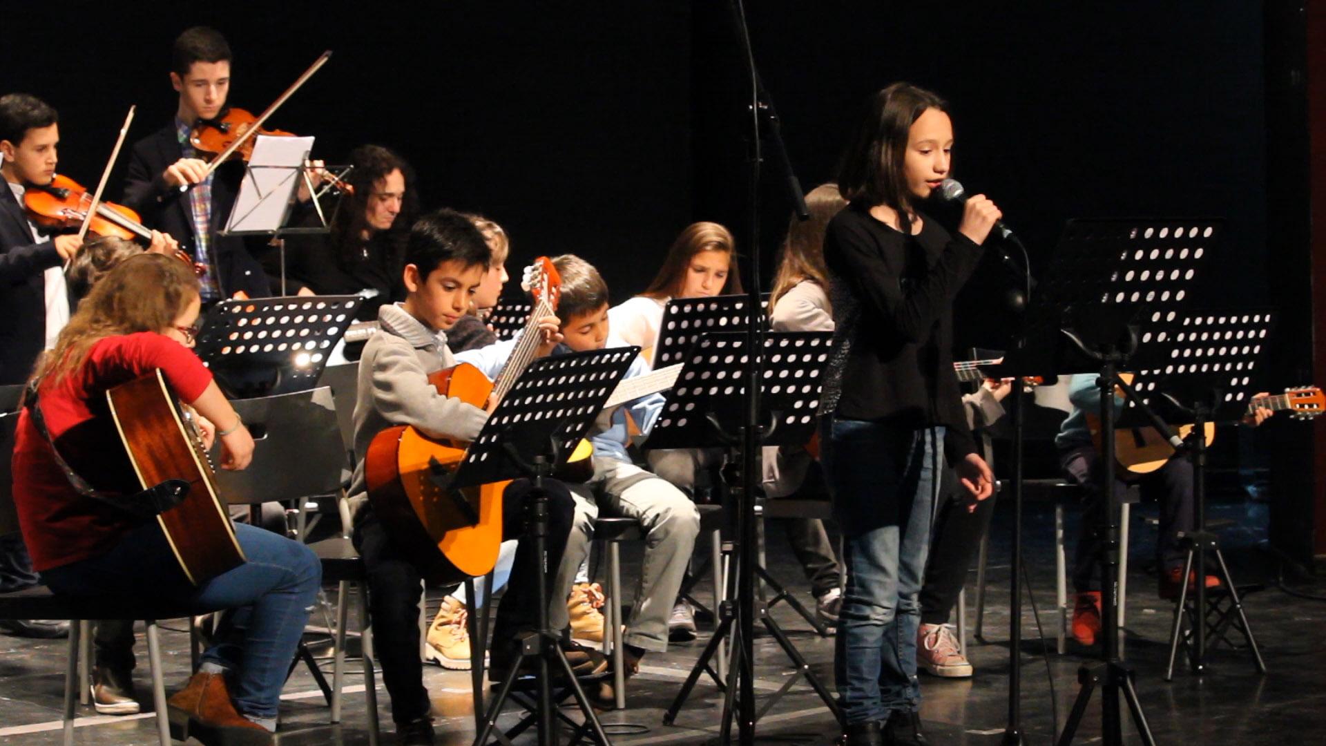 orquesta de niños y adultos con cantante en auditorio