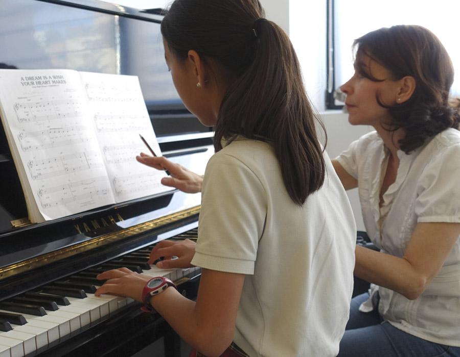 alumna de piano tocando mientras profesora explica partitura