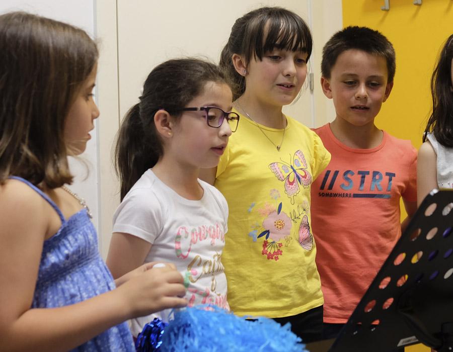 grupo de niños cantando mirando partitura en atril