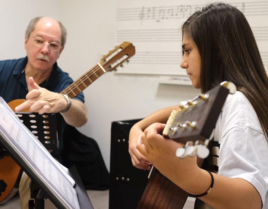 profesor explicando partitura a chica joven con guitarra