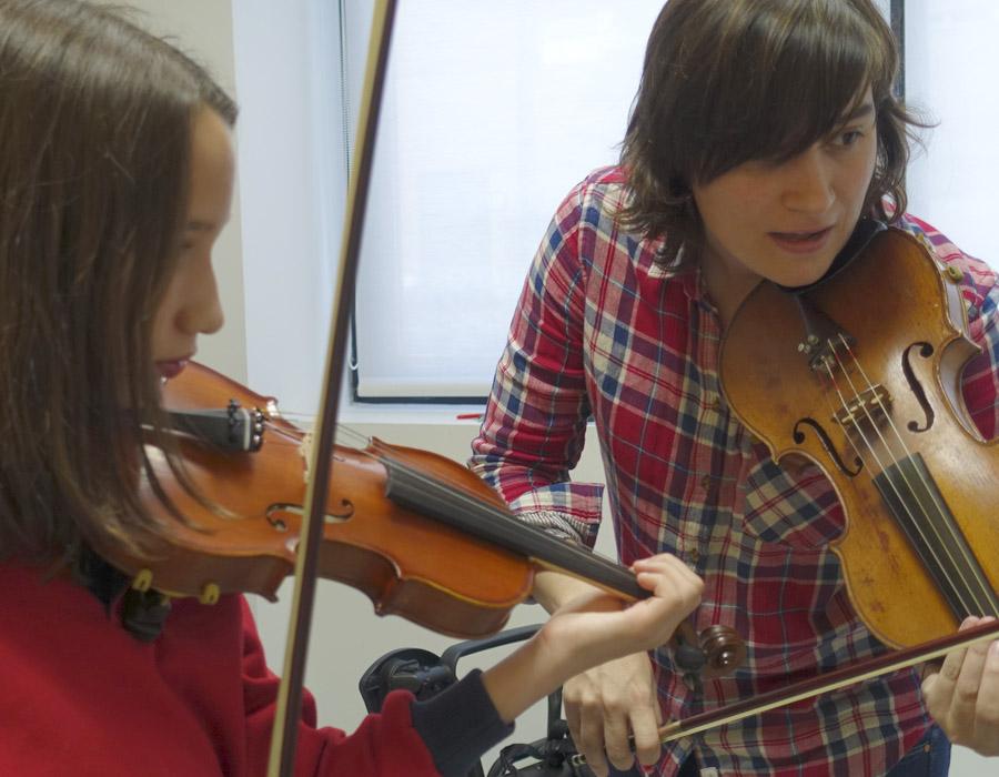 niña dando clase de violín junto a profesora