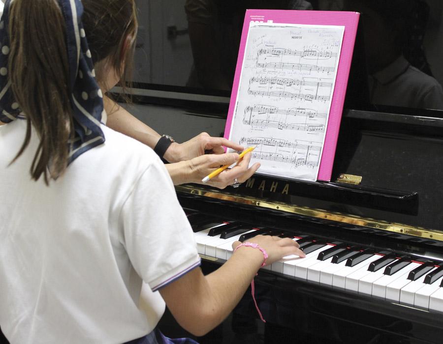 niña vestida de uniforme tocando piano junto a profesora