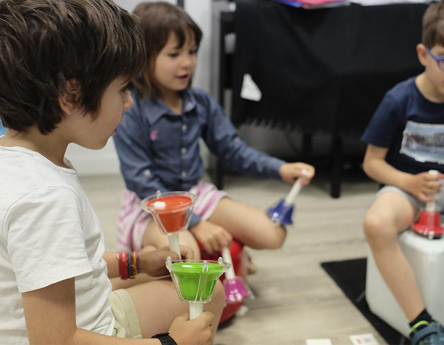 niños pequeños haciendo ritmos con campanas