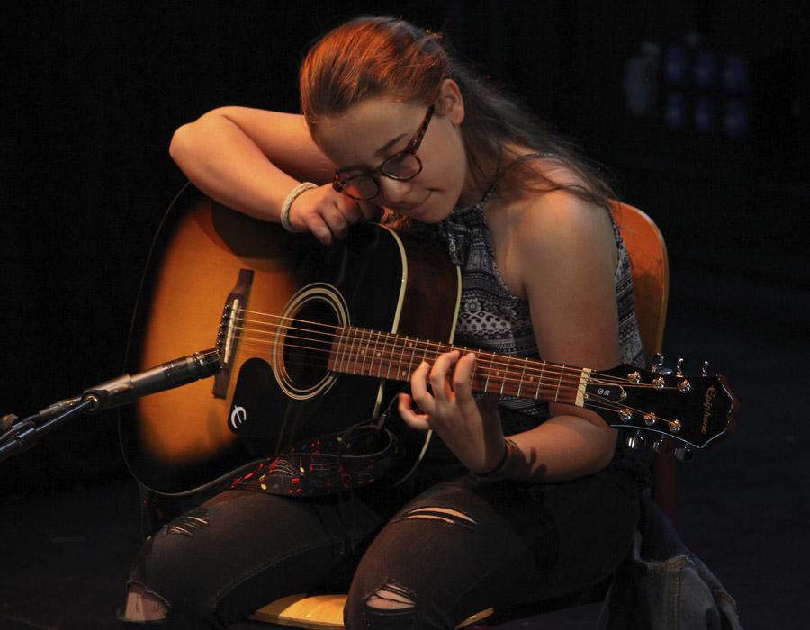 niña tocando guitarra española en auditorio