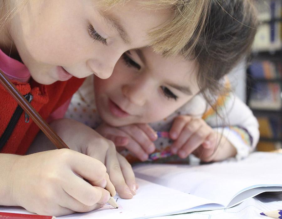 niñas pequeñas escribiendo juntas en libro de solfeo