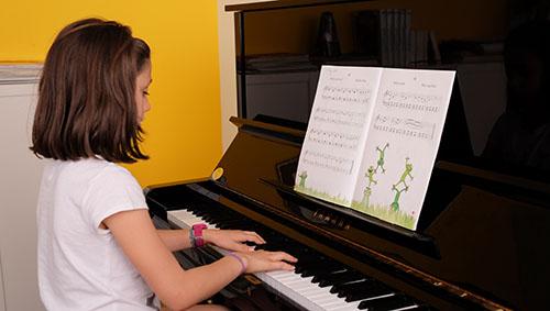 niña tocando piano vertical con partitura